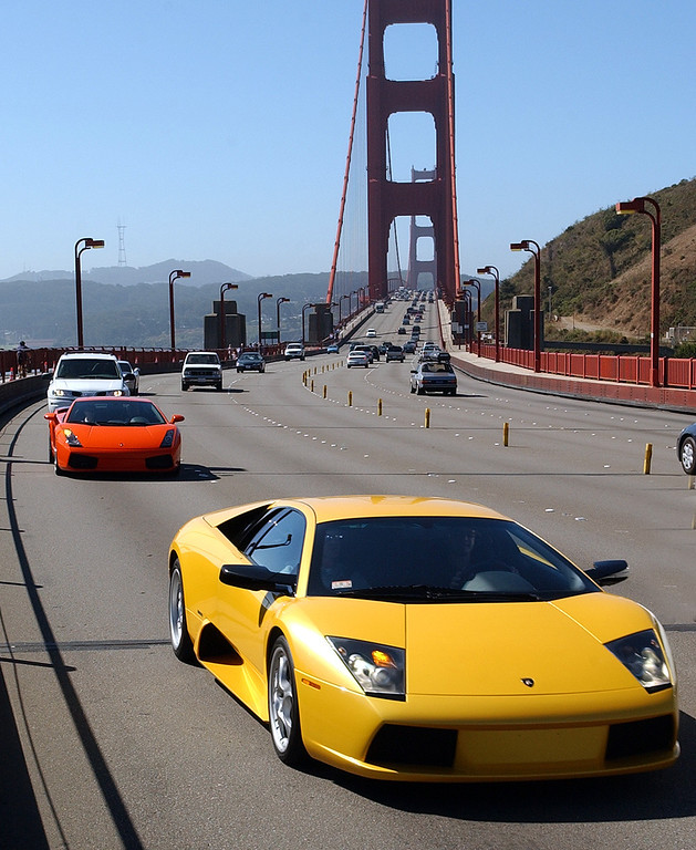 . A yellow Lamborghini Gallardo travels across the Golden Gate Bridge, Tuesday, Aug. 12, 2003,  in Sausalito, Calif. In celebration of Automobili Lamborghini\'s 40th anniversary and the North American premier of its 2004 Gallardo, the Italian car maker gathered a group of 40 different vehicles symbolizing the company\'s 40 years for a special ride from San Francisco City Hall through the Napa Valley, south to Monterey, Calif. (Photo/Ben Margot)