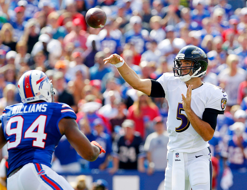 . Baltimore Ravens quarterback Joe Flacco (5) passes under pressure from Buffalo Bills defensive end Mario Williams (94) during the first half of an NFL football game on Sunday, Sept. 29, 2013, in Orchard Park, N.Y. (AP Photo/Bill Wippert)