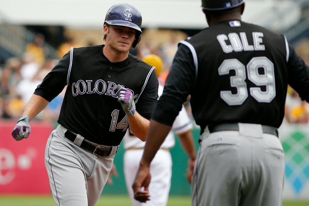 . Colorado Rockies\' Josh Rutledge, left, rounds third to greetings from Colorado Rockies third base coach Stu Cole, right, after hitting a two-run home run off Pittsburgh Pirates starting pitcher Jeff Locke during the first inning of a baseball game in Pittsburgh Sunday, July 20, 2014. (AP Photo/Gene J. Puskar)