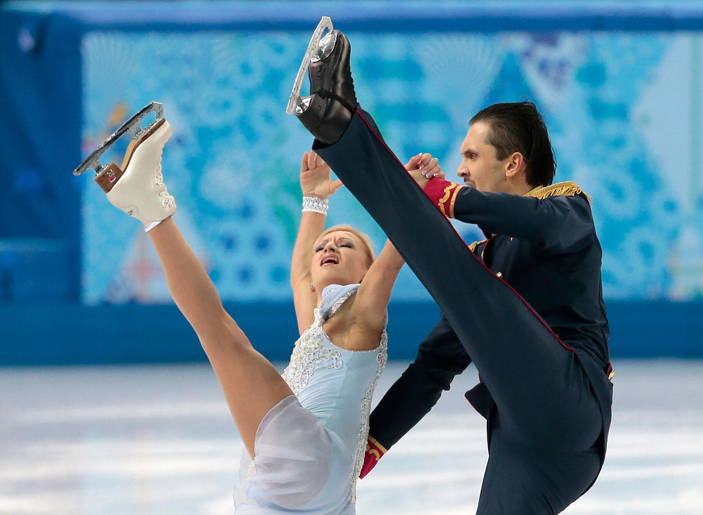 Description of . Tatiana Volosozhar and Maxim Trankov of Russia compete in the pairs short program figure skating competition at the Iceberg Skating Palace during the 2014 Winter Olympics, Tuesday, Feb. 11, 2014, in Sochi, Russia. (AP Photo/Ivan Sekretarev)