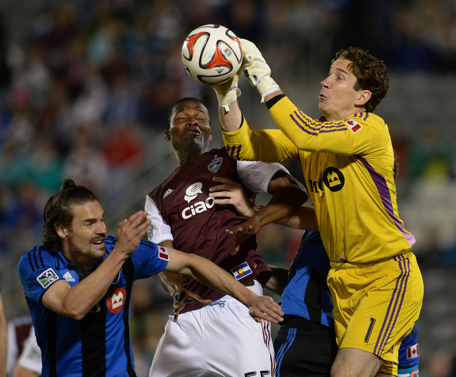 . Montreal goalkeeper Troy Perkins punched the ball away from Colorado forward Danny Mwanga (55) in the second half. The Colorado Rapids defeated the Montreal Impact 4-1 Saturday night, May 24, 2014. (Photo by Karl Gehring/The Denver Post)