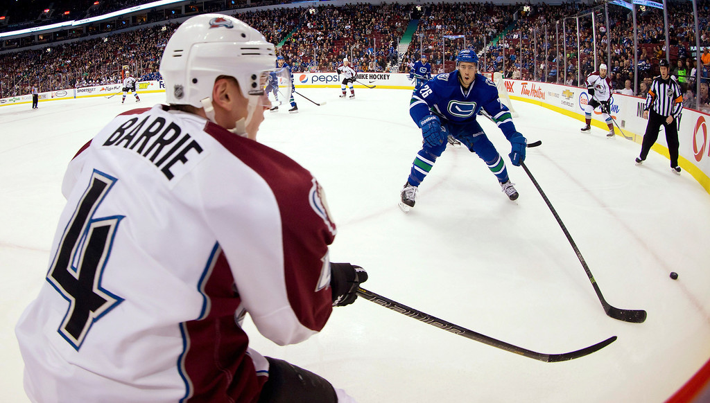 . Colorado Avalanche\'s Tyson Barrie, left, passes to teammate Ryan O\'Reilly, right, as Vancouver Canucks\' Frank Corrado, center, skates in to check him during the first period of an NHL hockey game Thursday, April 10, 2014, in Vancouver, British Columbia. (AP Photo/The Canadian Press, Darryl Dyck)