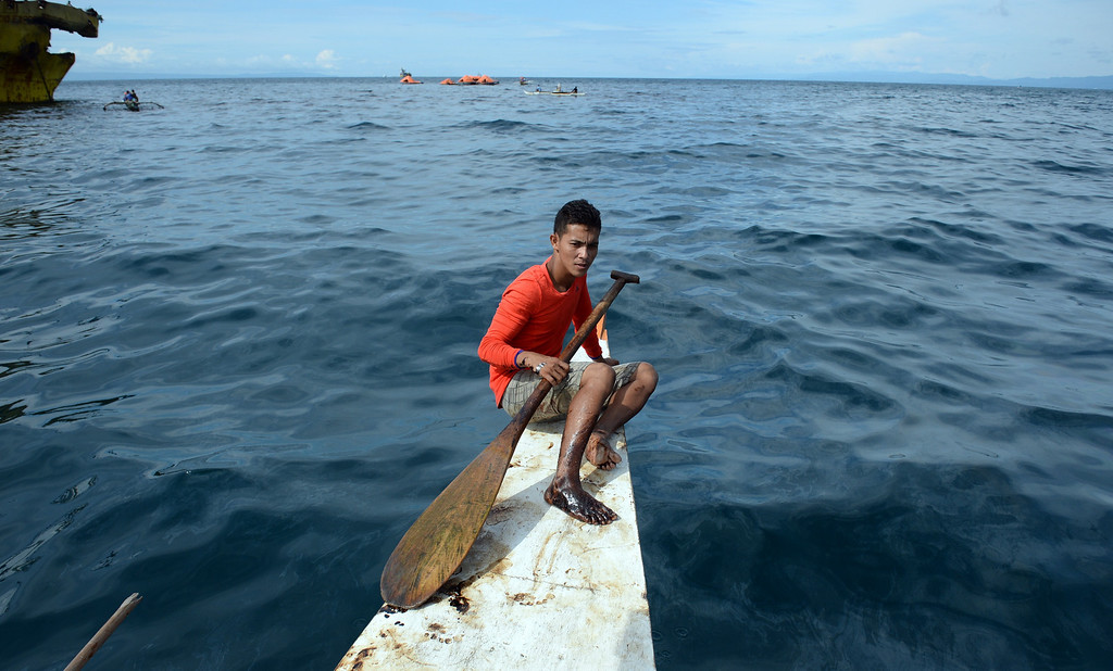 . A young fisherman with his right foot tainted with oil believed to be from the sunken ferry St. Thomas Aquinas sits at the bow of his boat on August 17, 2013 as rescue operations continue (in background) after the morning after the ferry collided with a cargo ship off the town of Talisay near the Philippines\' second largest city of Cebu. Philippine rescuers searched on August 17 for more than 200 people missing after the ferry collided with the cargo ship in thick darkness and sank almost instantly, with 26 already confirmed dead. TED ALJIBE/AFP/Getty Images