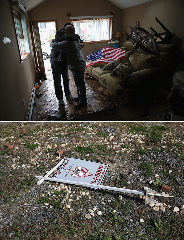 """. NEW YORK, NY - NOVEMBER 01: (top) Homeowner Michael Russo (R), is comforted by friend Joseph Bono on November 1, 2012 in the Ocean Breeze area of the Staten Island borough of New York City. The first floor of Russo\'s home was completely flooded by the ocean surge caused by superstorm Sandy. Russo said that he salvaged an American flag he had stored on the upper shelf of a supply closet.  NEW YORK, NY - OCTOBER 17:  (bottom)  A \""""for sale\"""" sign lies on an empty lot where Joseph Bono\'s home was demolished due to Hurricane Sandy flood damage on October 17, 2013 in the Ocean Breeze neighborhood of the Staten Island borough of New York City. Hurricane Sandy made landfall on October 29, 2012 near Brigantine, New Jersey and affected 24 states from Florida to Maine and cost the country an estimated $65 billion.   (Photos by John Moore/Getty Images)"""