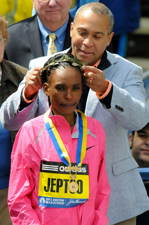 . Rita Jeptoo of Kenya is presented with the laurel wreath by Massachusetts Governor Deval Patrick after winning the women\'s division of the 117th Boston Marathon in Boston, Massachusetts April 15, 2013. REUTERS/Neal Hamberg