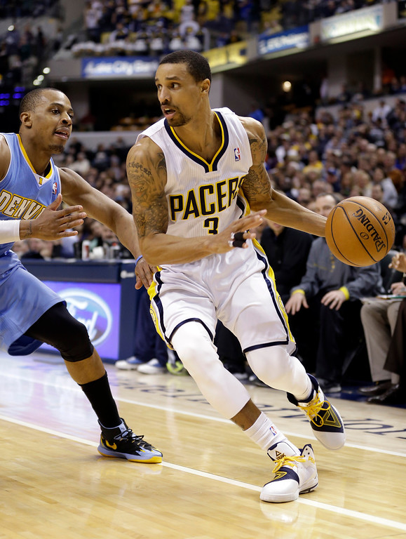 . Indiana Pacers guard George Hill, right, drives on Denver Nuggets guard Randy Foye in the second half of an NBA basketball game in Indianapolis, Monday, Feb. 10, 2014. The Pacers won 119-80. (AP Photo/Michael Conroy)