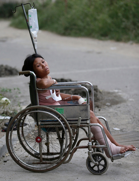 . An earthquake victim sits on a wheelchair outside a government hospital following a 7.2-magnitude quake that hit Cebu city in central Philippines Tuesday, Oct. 15, 2013. (AP Photo/Bullit Marquez)