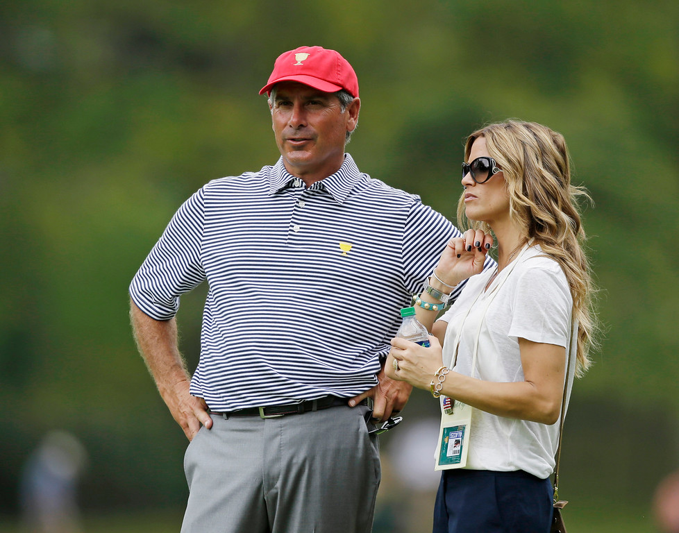 . United States team captain Fred Couples with his girlfriend Nadine Moze watch on the second hole during a foursome match against the International team at the Presidents Cup golf tournament at Muirfield Village Golf Club Friday, Oct. 4, 2013, in Dublin, Ohio. (AP Photo/Darron Cummings)