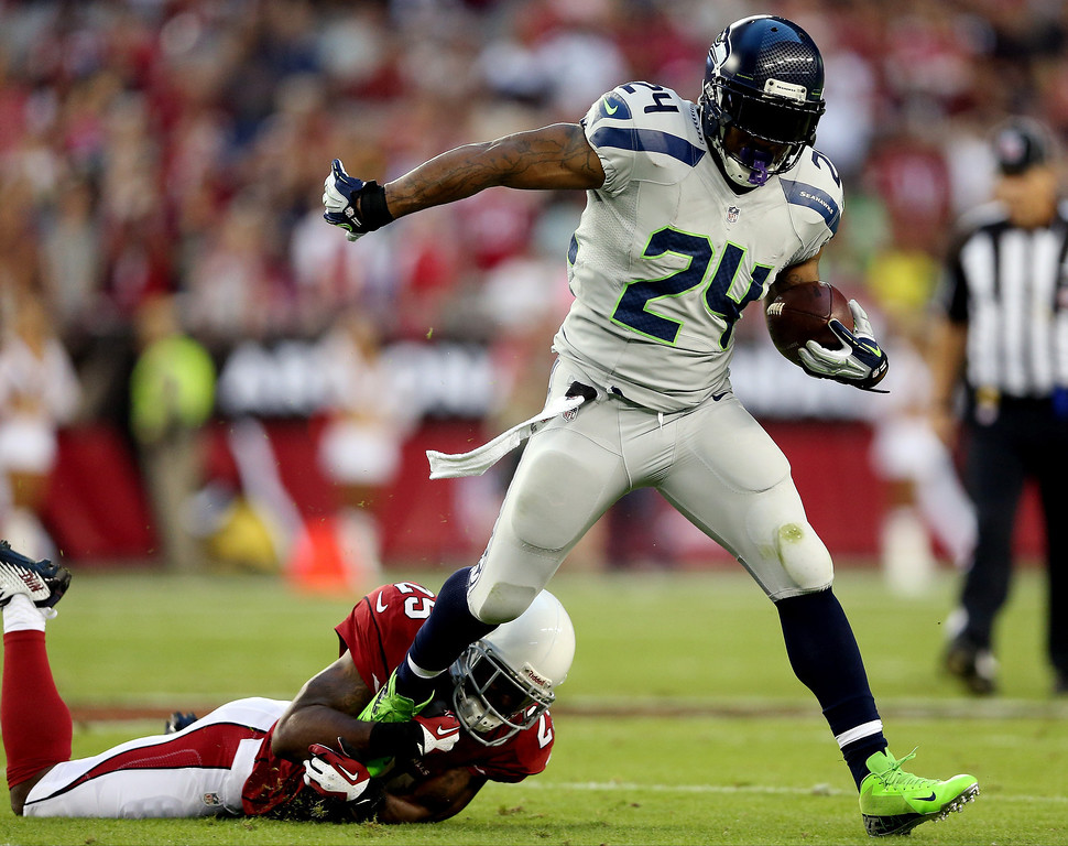 . GLENDALE, AZ - OCTOBER 17: Running back Marshawn Lynch #24 of the Seattle Seahawks runs with the ball as cornerback Jerraud Powers #25 of the Arizona Cardinals defends during a game at the University of Phoenix Stadium on October 17, 2013 in Glendale, Arizona.  (Photo by Christian Petersen/Getty Images)