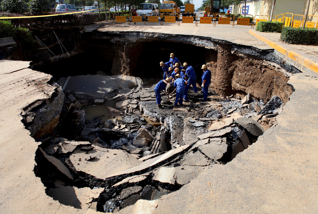 . Workers repair a cave-in area on a road in Xi\'an, Shaanxi province May 27, 2012. The cause of the cave-in, measuring about 6 meters (20 ft.) in depth, 15 meters (49 ft.) in length and 10 meters (33 ft.) in width, is still under investigation. No casualty has been reported, according to local media. Picture taken May 27, 2012.  REUTERS/China Daily