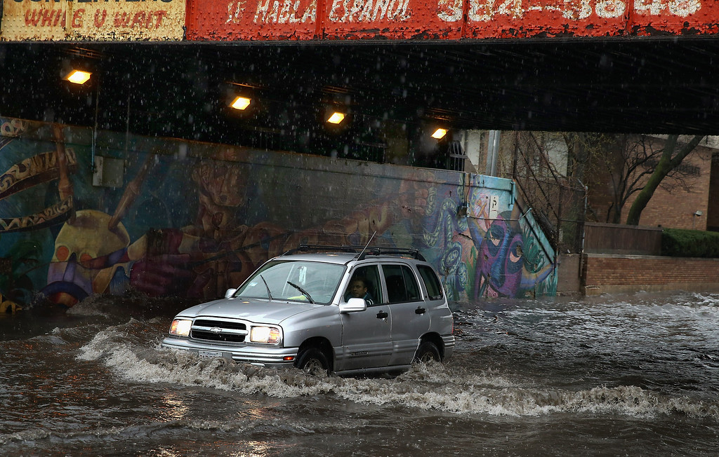 . A motorist drives through standing water in a flooded underpass on April 18, 2013 in Chicago, Illinois. Thunderstorms dumped up to 5 inches of rain on parts of the Chicago area overnight, closing sections the Edens, Eisenhower and Kennedy expressways, which lead into downtown, during the morning rush.  (Photo by Scott Olson/Getty Images)