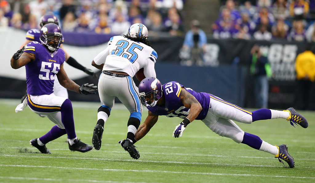 . Joique Bell #35 of the Detroit Lions carries the ball for a gain while Marvin Mitchell #55 and Chris Cook #20 of the Minnesota Vikings make the tackle on December 29, 2013 at Mall of America Field at the Hubert H. Humphrey Metrodome in Minneapolis, Minnesota. (Photo by Adam Bettcher/Getty Images)