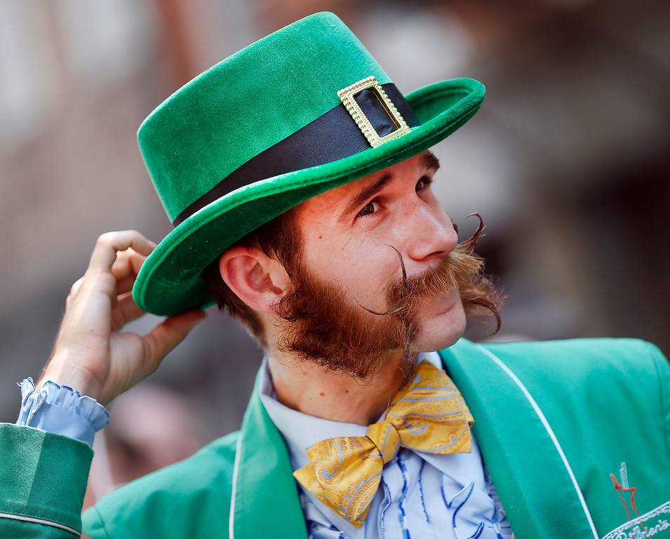 . Pierre Dupleix of New Orleans, a bartender at the famed Pat O\'Brien\'s bar in the French Quarter, adjusts his hat while participating in a parade through the French Quarter kicking off the fourth annual Just For Men National Beard and Moustache Championships Saturday, Sept. 7, 2013 in New Orleans. Dupleix said it took him five months to grow his sideburns. Contestants competed in 18 different categories including Dali, full beard natural and sideburns. (AP Photo/Susan Poag)