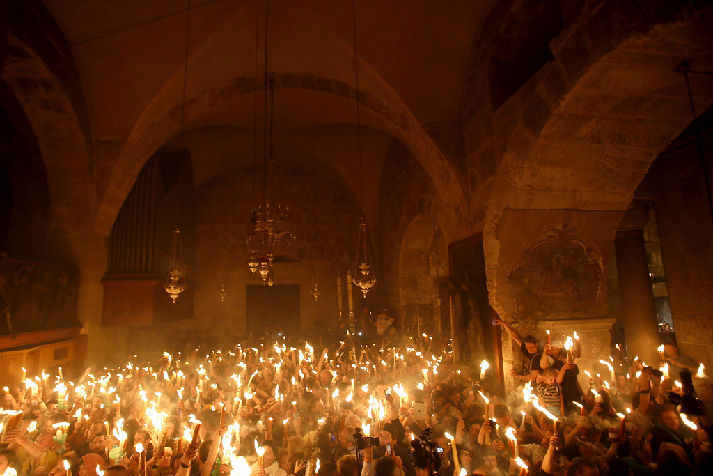 ". Christian Orthodox worshippers hold up candles lit from the ""Holy Fire\"" as thousands gather in the Church of the Holy Sepulchre in Jerusalem\'s old city on April 19, 2014 during the \""Holy Fire\"" ceremony on the eve of the Orthodox Easter.  AFP PHOTO/GALI TIBBON/AFP/Getty Images"