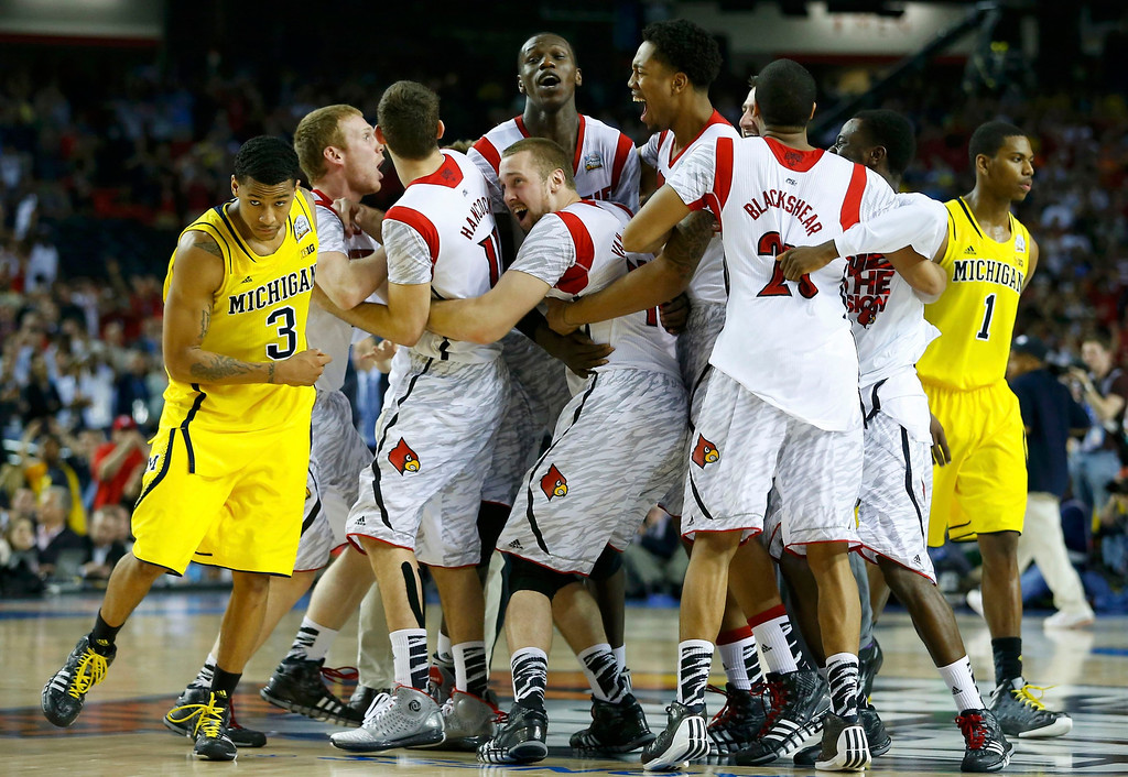 . The Louisville Cardinals celebrate as Michigan Wolverines guard Trey Burke (L) and forward Glenn Robinson III leave the court after Louisville won the NCAA men\'s Final Four championship basketball game in Atlanta, Georgia April 8, 2013. REUTERS/Jeff Haynes