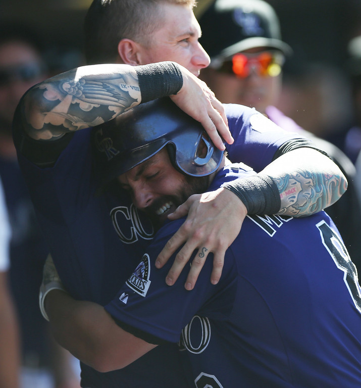 . Colorado Rockies\' Michael McKenry, front, hugs Brandon Barnes while returning to the dugout after hitting a solo home run in the sixth inning of their 9-2 victory in a baseball game against the San Francisco Giants in Denver, Wednesday, Sept. 3, 2014. (AP Photo/David Zalubowski)