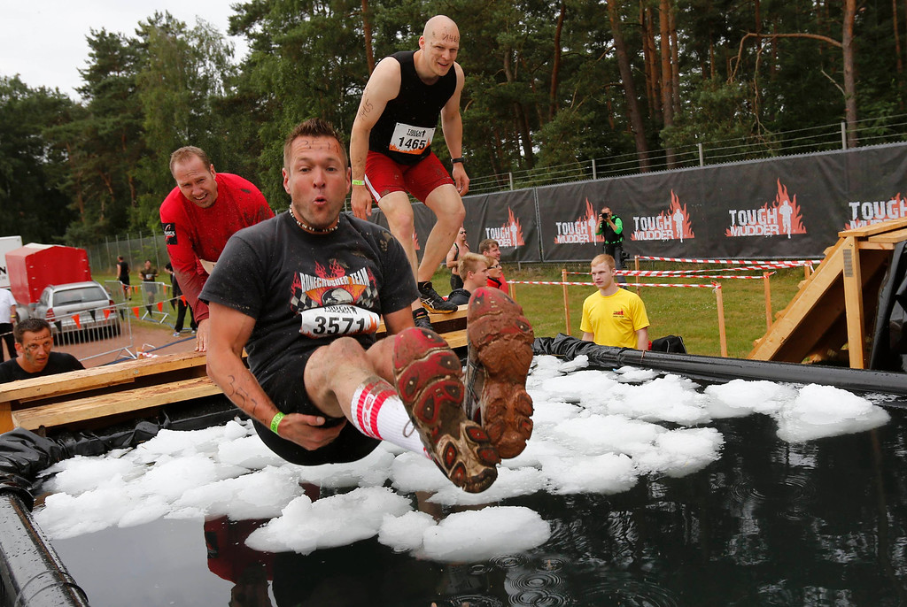 """. A participant of \""""Tough Mudder\"""" endurance event series jumps into a tub filled with ice-cubes at the \""""Arctic Enema\"""" obstacle in the Fursten Forest, a former British Army training ground near the north-western German city of Osnabrueck July 13, 2013. The hardcore but un-timed event over 16 km (10 miles) was designed by British Special Forces to test mental as well as physical strength. Some 4,000 competitors had to overcome obstacles of common human fears, such as fire, water, electricity and heights.   REUTERS/Wolfgang Rattay"""