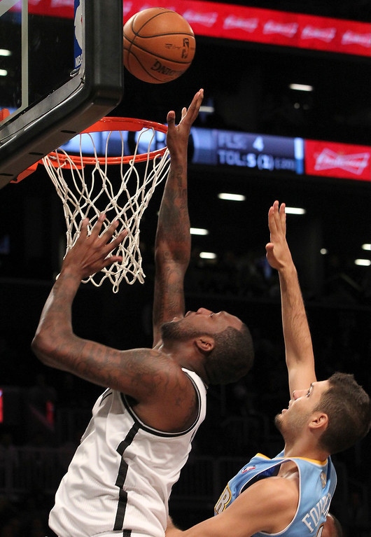 . Brooklyn Nets\' Andray Blatche, left, goes up past Denver Nuggets\' Evan Fournier (94) during the first half of an NBA basketball game, Wednesday, Feb. 13, 2013, at Barclays Center in New York.  (AP Photo/Mary Altaffer)