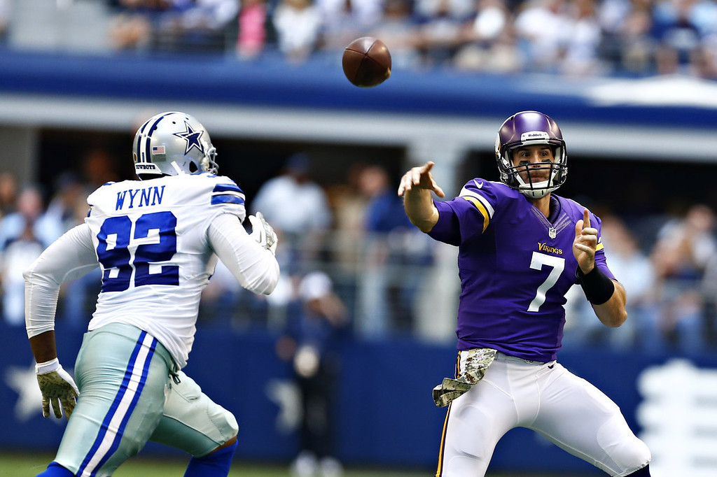 . Christian Ponder #7 of the Minnesota Vikings throws a pass under pressure from Jarius Wynn #92 of the Dallas Cowboys at  AT&T Stadium on November 3, 2013 in Arlington, Texas.  (Photo by Wesley Hitt/Getty Images)