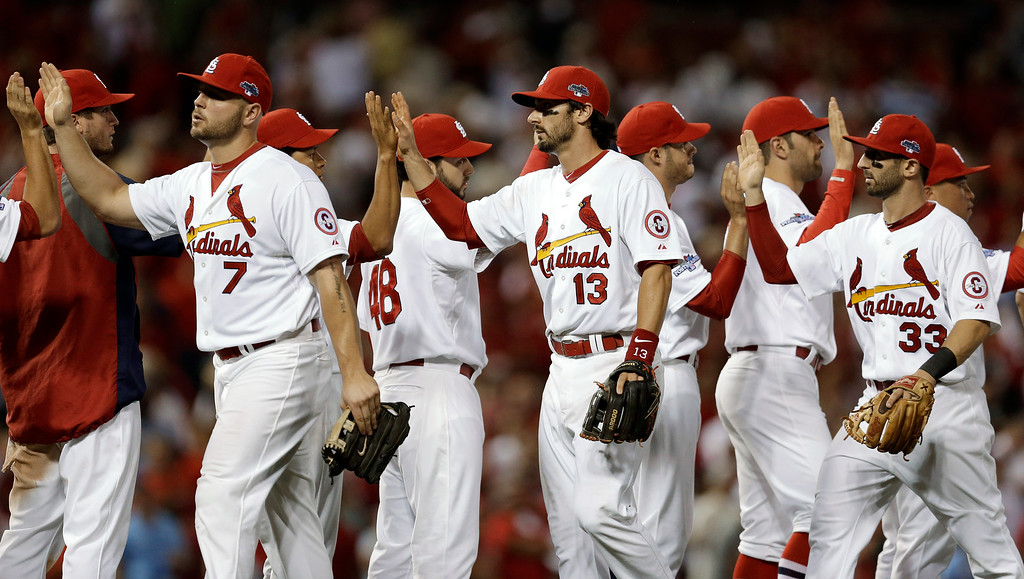 . St. Louis Cardinals, including Matt Holliday (7), Matt Carpenter (13) and Daniel Descalso (33), celebrate after defeating the Pittsburgh Pirates 9-1 in Game 1 of baseball\'s National League division series, Thursday, Oct. 3, 2013, in St. Louis. (AP Photo/Jeff Roberson)