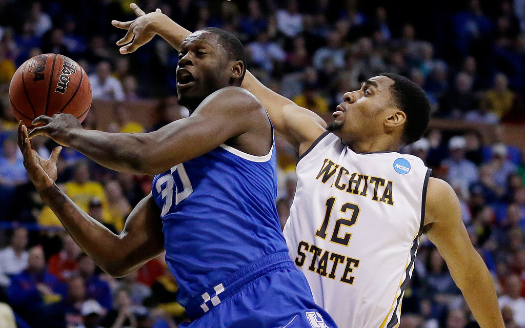. Kentucky forward Julius Randle (30) passes around Wichita State forward Darius Carter (12) during the first half of a third-round game of the NCAA college basketball tournament Sunday, March 23, 2014, in St. Louis. (AP Photo/Jeff Roberson)