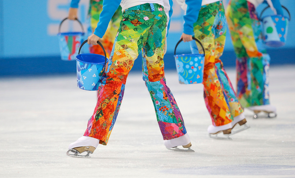 . Volunteers take to the ice to repair the surface during a break to resurface the ice in the pairs free skate figure skating competition at the Iceberg Skating Palace during the 2014 Winter Olympics, Wednesday, Feb. 12, 2014, in Sochi, Russia. (AP Photo/Vadim Ghirda)
