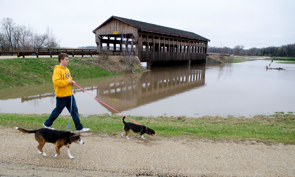 . Cody Weets walks his dogs along the flooded Rock Creek  in Morrison, Ill., Thursday, April 18, 2013. Torrential rains swept throughout the area with many rivers surging beyond their banks from the downpours in Missouri, Iowa and Illinois. (AP Photo/Sauk Valley Media, Philip Marruffo)