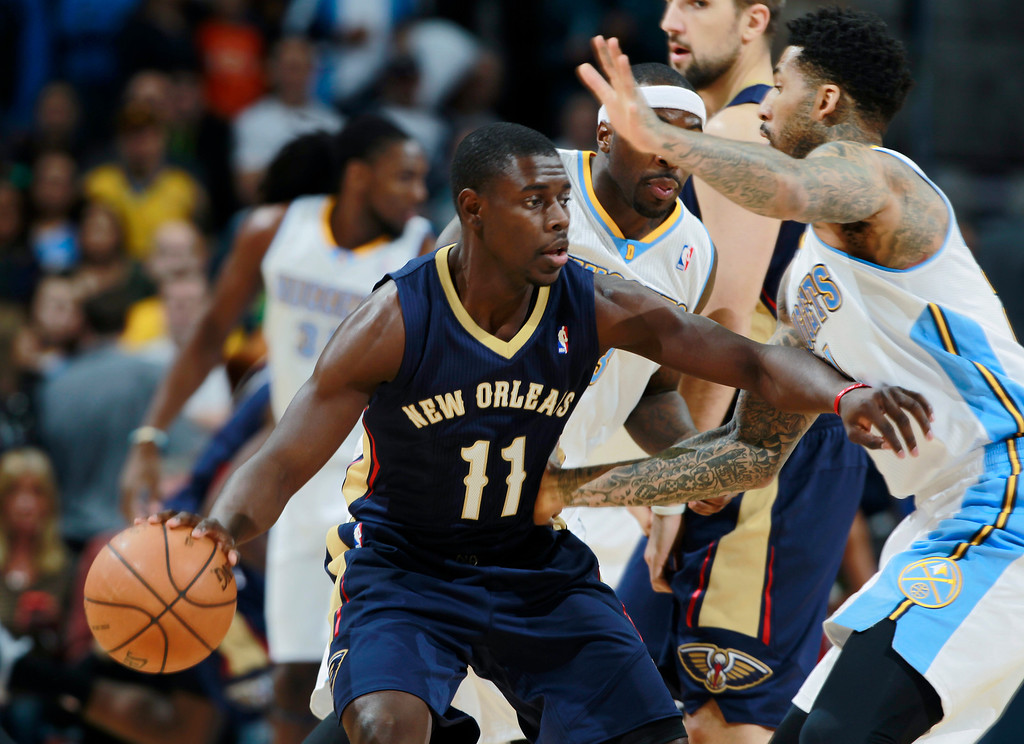 . New Orleans Pelicans guard Jrue Holiday, left, picks up a loose ball as Denver Nuggets guard Ty Lawson, back left, and forward Wilson Chandler get tangled up while trying to cover Holiday in the first quarter of an NBA basketball game in Denver on Sunday, Dec. 15, 2013. (AP Photo/David Zalubowski)