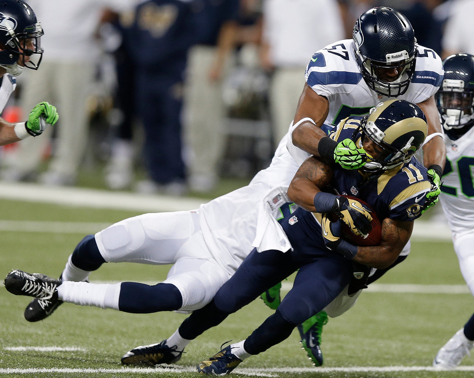 . Seattle Seahawks outside linebacker Mike Morgan (57) tackles St. Louis Rams wide receiver Tavon Austin (11) during the second half of an NFL football game, Monday, Oct. 28, 2013, in St. Louis. (AP Photo/Michael Conroy)