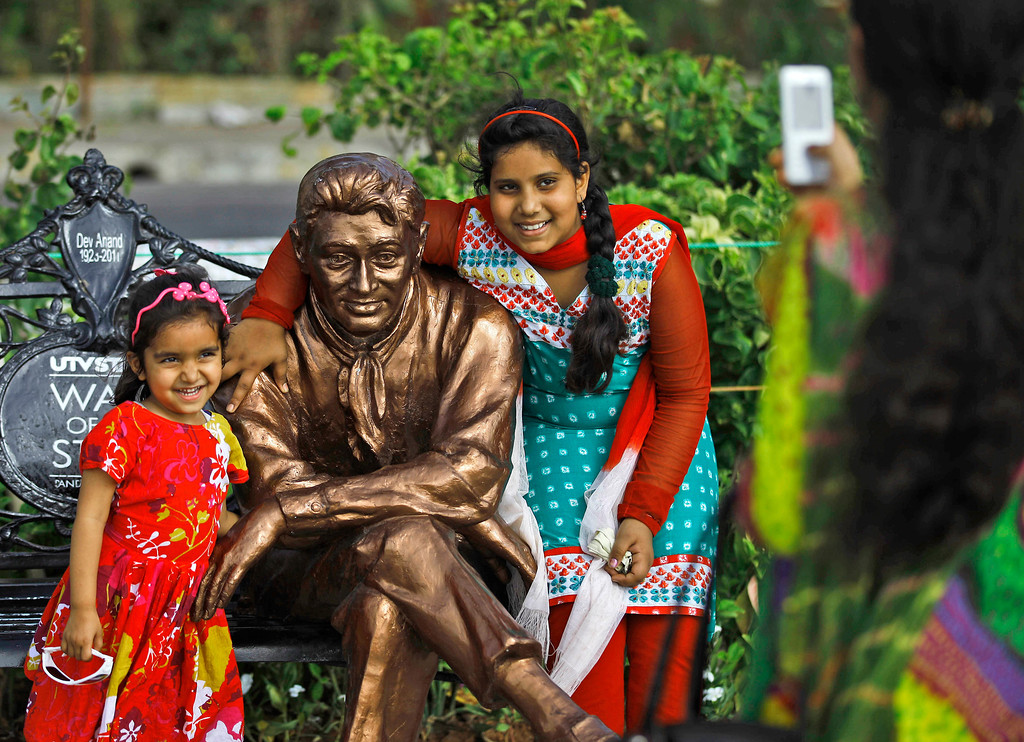 ". In this April 18, 2013 photo, Indian children pose for photographs with a statue of late Bollywood star Dev Anand in Mumbai, India. Friday, May 3 marks exactly a hundred years after India\'s first feature film ""Raja Harischandra,\"" a silent movie, was screened in 1913. India produced almost 1,500 movies last year and the industry is expected to grow from $ 2 billion to $ 3.6 billion in the next five years, according to consultancy KPMG. (AP Photo/Rafiq Maqbool)"