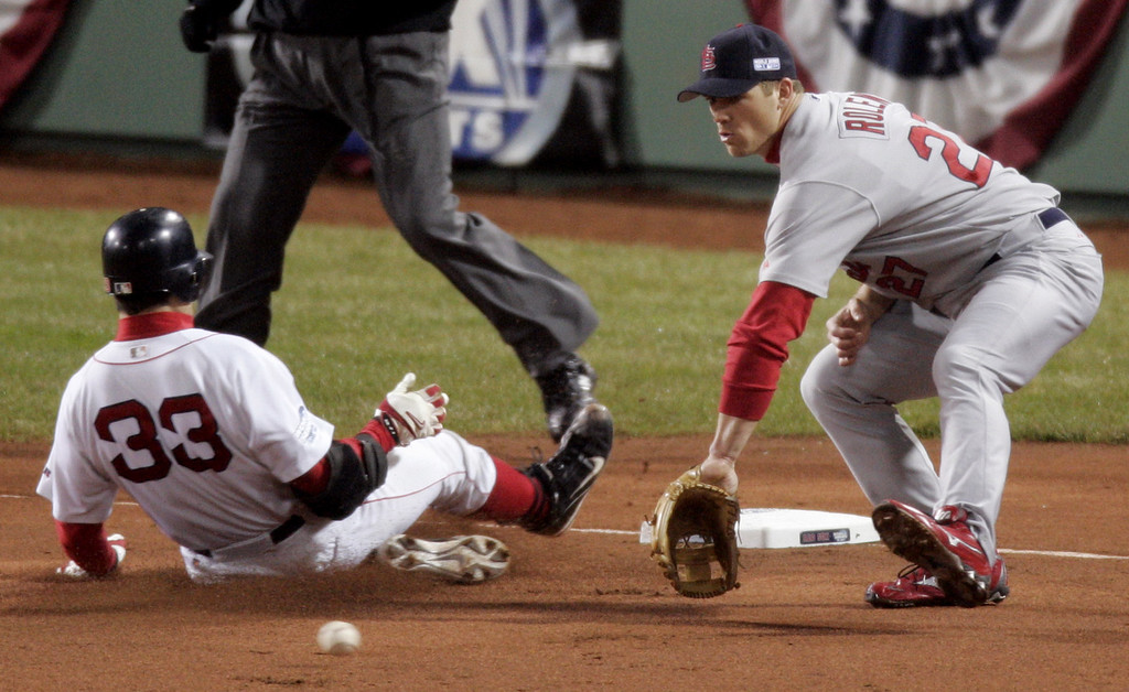 . Boston Red Sox Jason Varitek, left, wins the race to the base for a triple against the St. Louis Cardinals and third baseman Scott Rolen in the first inning of  game two of the World Series in Boston, Sunday, Oct. 24, 2004. (AP Photo/Amy Sancetta)