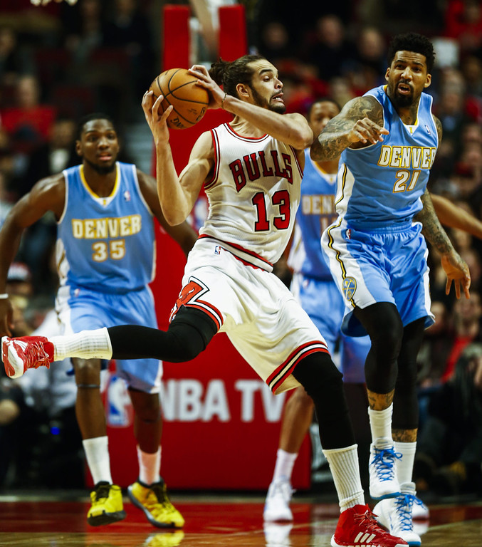 . Chicago Bulls center Joakim Noah (C) pulls a rebound away from Denver Nuggets forward Wilson Chandler (R) in the first half of their NBA game at the United Center in Chicago, Illinois, USA, 21 February 2014  EPA/TANNEN MAURY