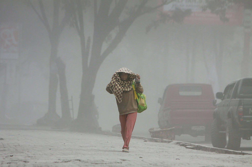 . A villager walks under heavy ashfall after a fresh eruption of Mount Sinabung volcano covered Karo district and other areas on September 17, 2013. Thousands of villagers fled after Mount Sinabung\'s series of volcanic eruptions on Indonesia\'s Sumatra island, spewing rocks and red-hot ash onto surrounding villages, officials said.    KHARISMA TARIGAN/AFP/Getty Images