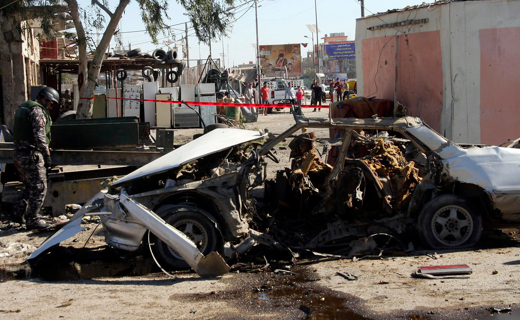 . A policeman stands guard at the site of car bomb attack in Baghdad\'s Sadr City March 19, 2013.  REUTERS/Qahtan al-Sudani