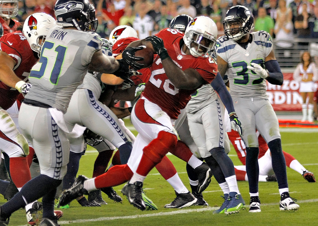 . Arizona Cardinals running back Rashard Mendenhall (28) scores a touchdown as Seattle Seahawks outside linebacker Bruce Irvin (51) defends during the first half of an NFL football game, Thursday, Oct. 17, 2013, in Glendale, Ariz. (AP Photo/Rick Scuteri)