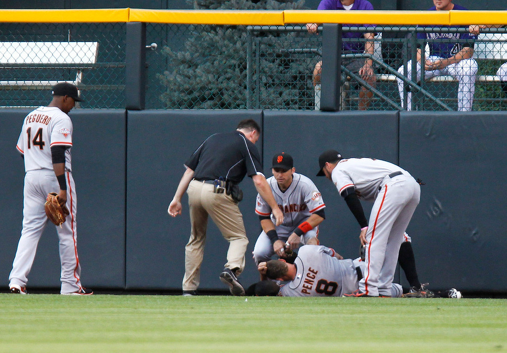 . San Francisco Giants right fielder Hunter Pence (8) is attended to after hitting the right-field wall chasing a fly ball by Colorado Rockies\' Michael Cuddyer during the first inning of a baseball game, Monday, Aug. 26, 2013, in Denver. (AP Photo/Barry Gutierrez)
