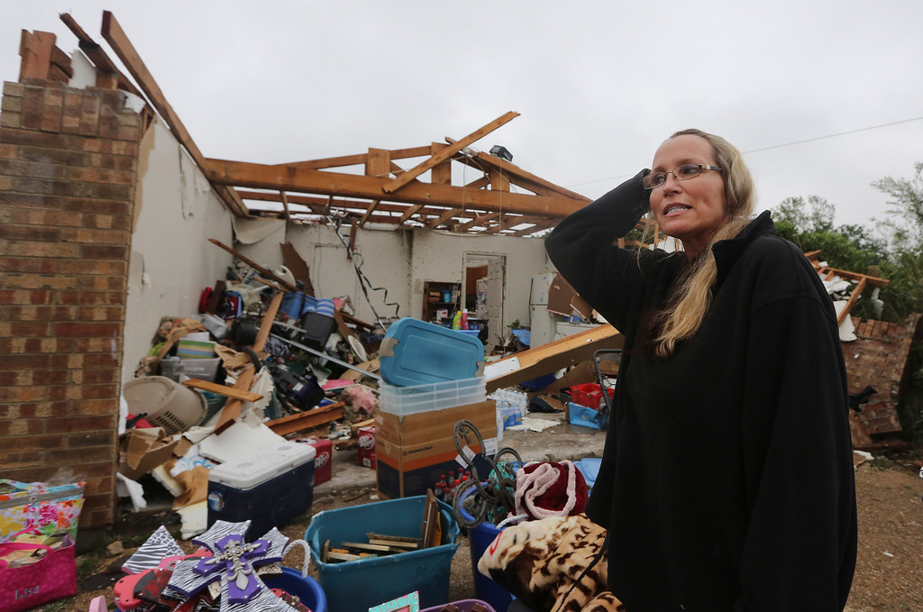 . Lisa Montgomery pauses as she talks about surviving a tornado that destroyed her home in Cleburne, Texas, Thursday, May 16, 2013.  Ms. Montgomery rode out the twister the night before in her bathtub with her 10-year-old son and is salvaging items with friends and family helping.  (AP Photo/LM Otero)