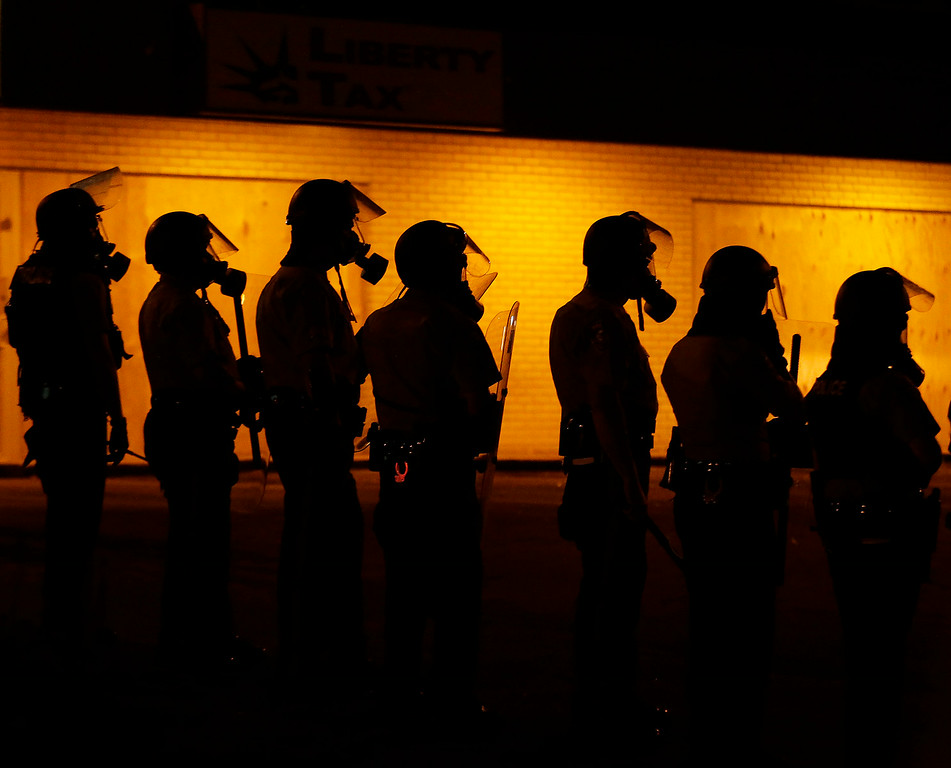 . Police wait to advance after tear gas was used to disperse a crowd Sunday, Aug. 17, 2014, druing a protest for Michael Brown, who was killed by a police officer last Saturday in Ferguson, Mo. As night fell Sunday in Ferguson, another peaceful protest quickly deteriorated after marchers pushed toward one end of a street. Police attempted to push them back by firing tear gas and shouting over a bullhorn that the protest was no longer peaceful. (AP Photo/Charlie Riedel)
