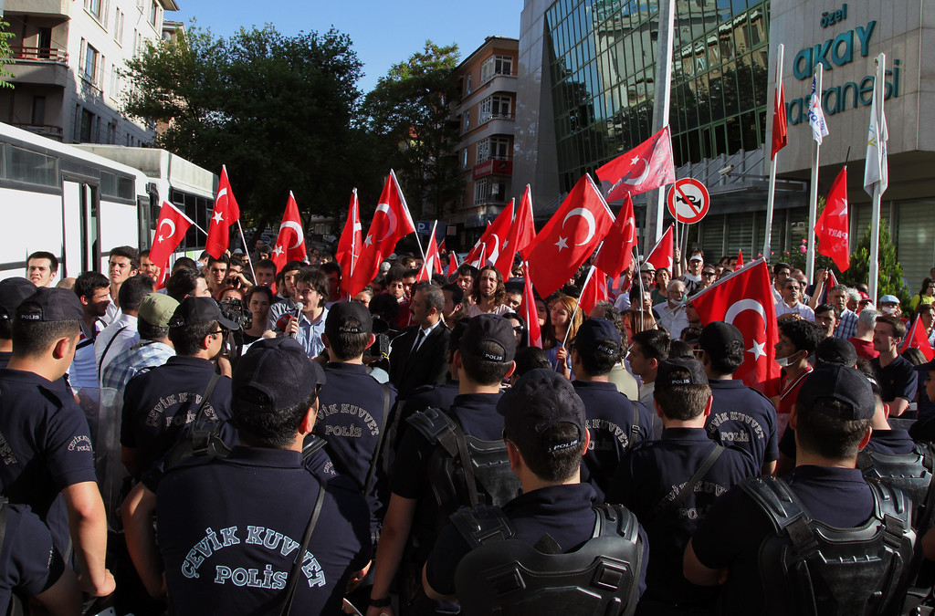 . Riot police confront dozens of Turks who are staging a protest outside a hotel hosting a group of journalists, academics and artists who have been appointed by the government to promote a peace process with the Kurdish PKK rebels, in Ankara, Turkey, Tuesday, May 7, 2013. The rebels of the Kurdistan Workersí Party, or PKK, reaffirmed that it will start withdrawing forces from Turkey to bases in northern Iraq on Wednesday, as part of the peace talks aimed at ending the nearly three-decade-long conflict that has killed tens of thousands of people.(AP Photo/Burhan Ozbilici)