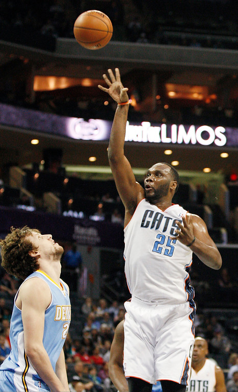 . Charlotte Bobcats center Al Jefferson, right, shoots over Denver Nuggets forward Jan Vesely, of the Czech Republic, during the first half of an NBA basketball game in Charlotte, N.C., Monday, March 10, 2014. (AP Photo/Nell Redmond)