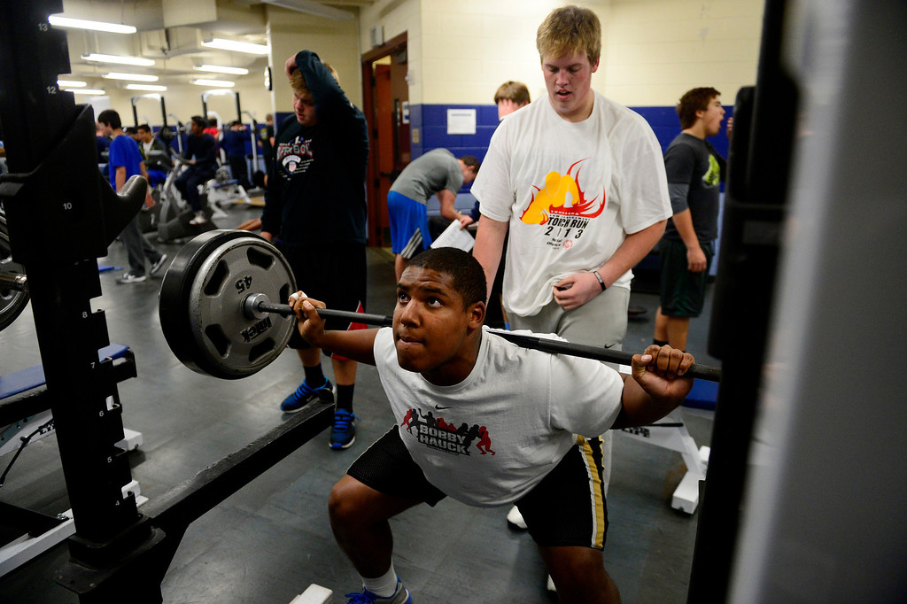 . Valor Christian starting right tackle Isaiah Holland squats while being spotted by left tackle Alec Ruth during a lift.   (Photo by AAron Ontiveroz/The Denver Post)