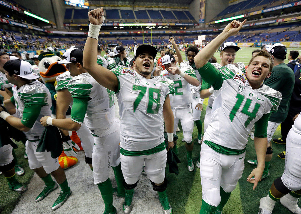 . Oregon celebrate the team\'s win with the band in the Valero Alamo Bowl NCAA college football game against Texas, Monday,  Dec. 30, 2013, in San Antonio. Oregon won 30-7. (AP Photo/Eric Gay)
