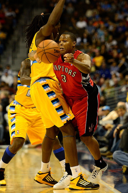 . Toronto Raptors point guard Kyle Lowry (3) squeezes a pass by Denver Nuggets small forward Kenneth Faried (35) during the second half of the Nuggets\' 113-110 win at the Pepsi Center on Monday, December 3, 2012. AAron Ontiveroz, The Denver Post