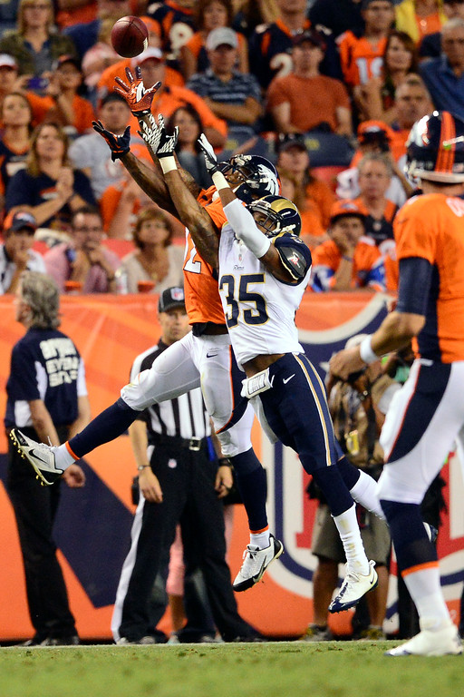 . DENVER, CO - AUGUST 24: Andre Caldwell (12) of the Denver Broncos cannot haul in a touchdown catch as Darren Woodard (35) of the St. Louis Rams defends during the first half of action of an NFL preseason game at Sports Authority Field at Mile High on August 24, 2013. This is the third game of the preseason for the Broncos. (Photo by AAron Ontiveroz/The Denver Post)
