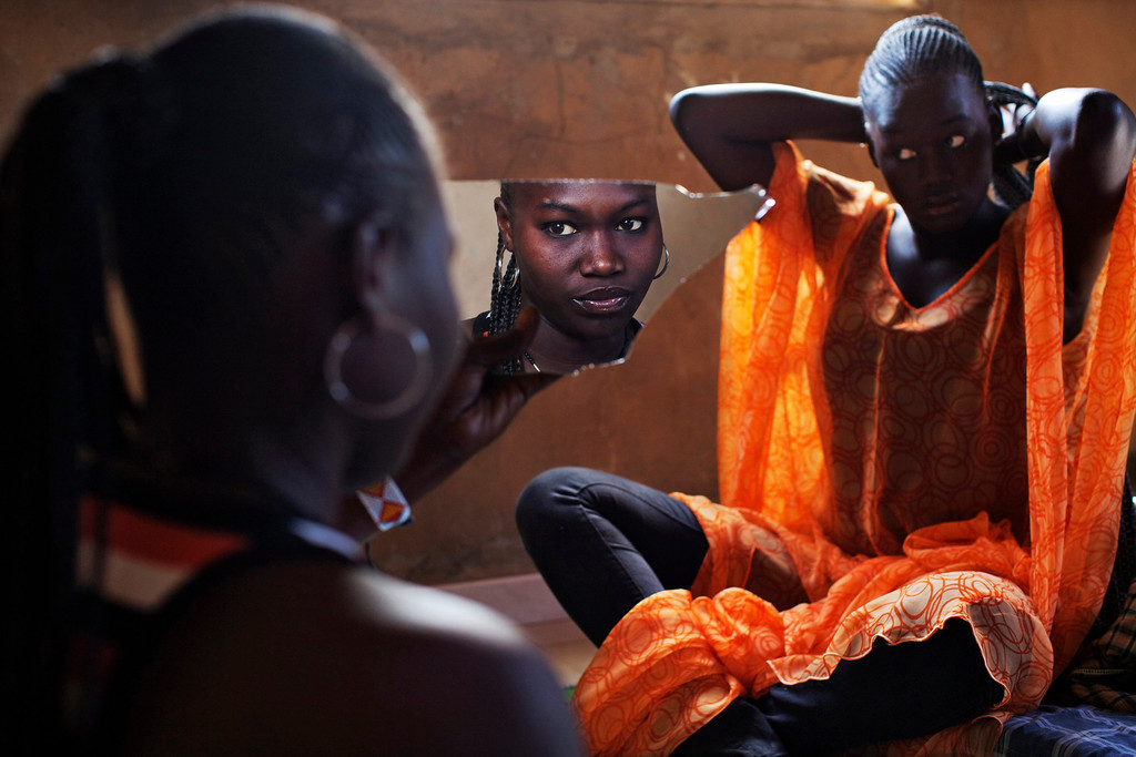 . Bineta Ndiaye, 22, looks at herself in the mirror as her friend Coumba Faye, 19, fixes her hair in Faye\'s house in the village of Ndande, May 19, 2013. Every year, inhabitants of the village take part in a Sufi Muslim ceremony called Gamou-Ndande. The ceremony combines nights of praying and chanting as well as traditionally animist ceremonies. Picture taken May 19, 2013.  REUTERS/Joe Penney