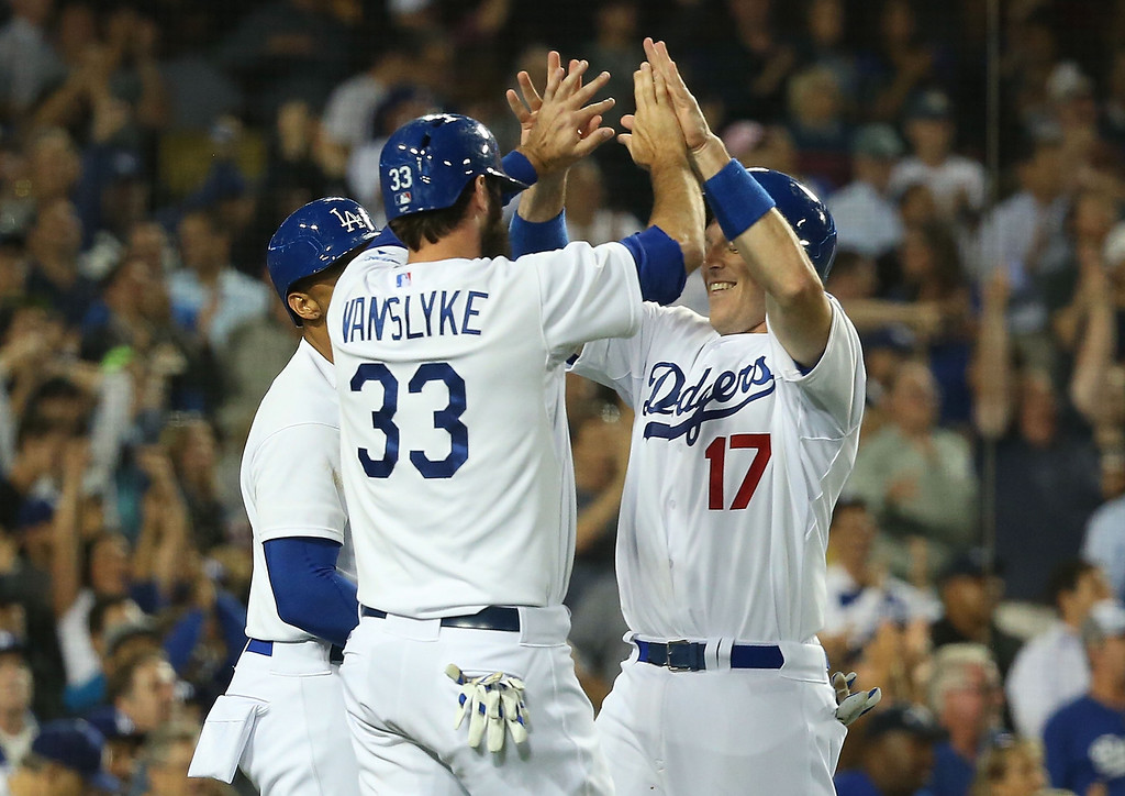 . Scott Van Slyke #33 and A.J. Ellis #17 of the Los Angeles Dodgers celebrate after scoring in the third inning during the MLB game against the Colorado Rockies at Dodger Stadium on June 18, 2014 in Los Angeles, California.  (Photo by Victor Decolongon/Getty Images)