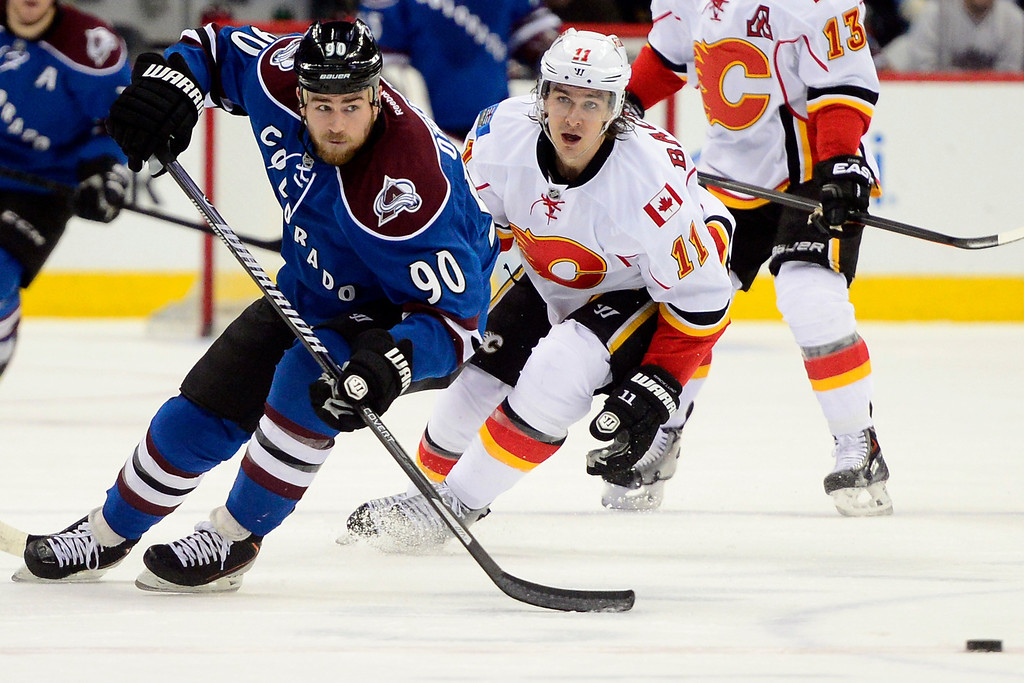 . Ryan O\'Reilly (90) of the Colorado Avalanche brings the puck up the ice as Mikael Backlund (11) of the Calgary Flames pursues during the first period during their game at the Pepsi Center in Denver on Monday, Jan. 4, 2014. (Photo by AAron Ontiveroz/The Denver Post)