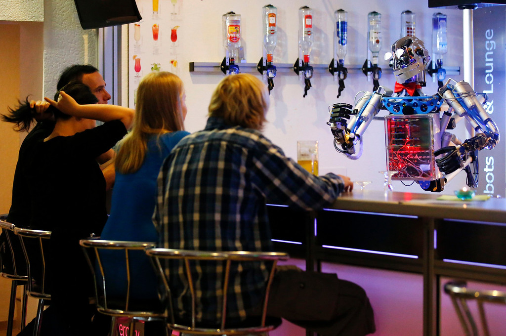 """. Humanoid robot bartender \""""Carl\"""" gestures to guests at the Robots Bar and Lounge in the eastern German town of Ilmenau, July 26, 2013. \""""Carl\"""", developed and built by mechatronics engineer Ben Schaefer who runs a company for humanoid robots, prepares spirits for the mixing of cocktails and is able to interact with customers in small conversations. Picture taken July 26, 2013. REUTERS/Fabrizio Bensch"""