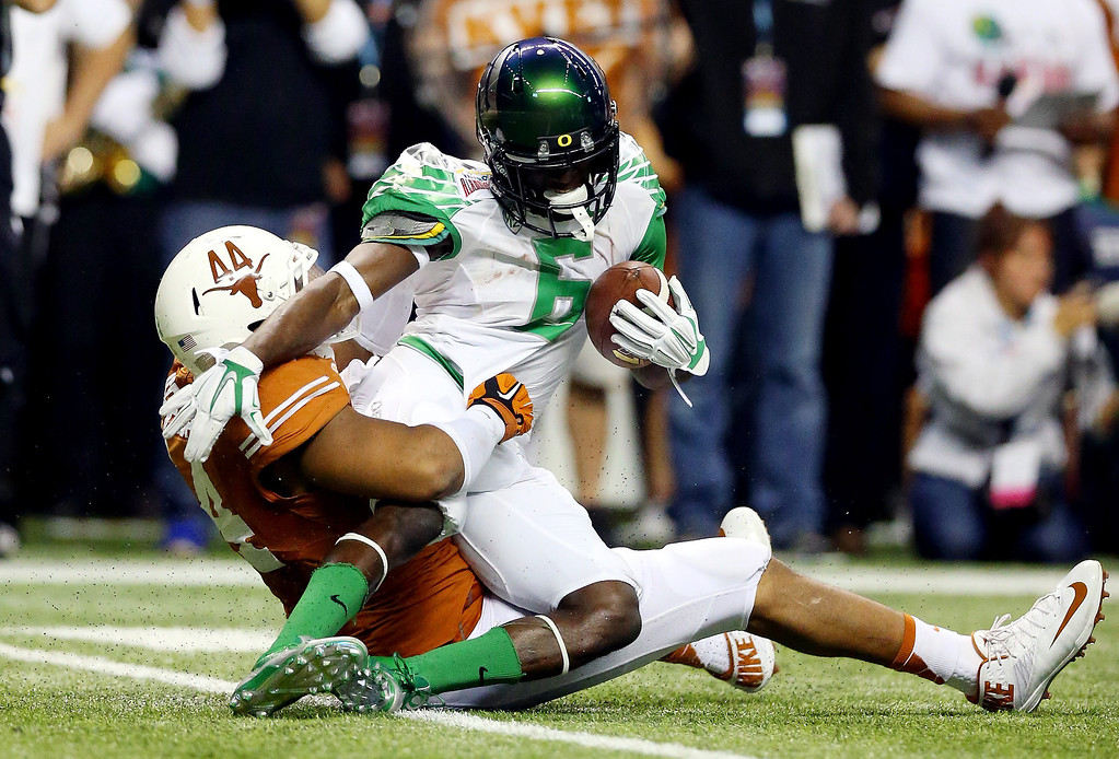. Running back De\'Anthony Thomas #6 of the Oregon Ducks is tackled by defensive end Jackson Jeffcoat #44 of the Texas Longhorns in the second quarter of the Valero Alamo Bowl at the Alamodome on December 30, 2013 in San Antonio, Texas.  (Photo by Ronald Martinez/Getty Images)