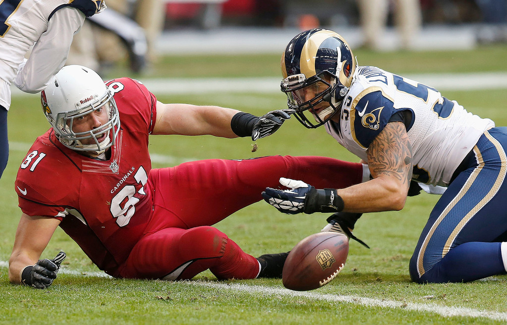 . Arizona Cardinals\' Jim Dray (81) and St. Louis Rams\' James Laurinaitis, right, scramble after the ball after Dray fumbled the ball during the first half of an NFL football game on Sunday, Dec. 8, 2013, in Glendale, Ariz.  The Rams recovered the ball on the play. (AP Photo/Ross D. Franklin)